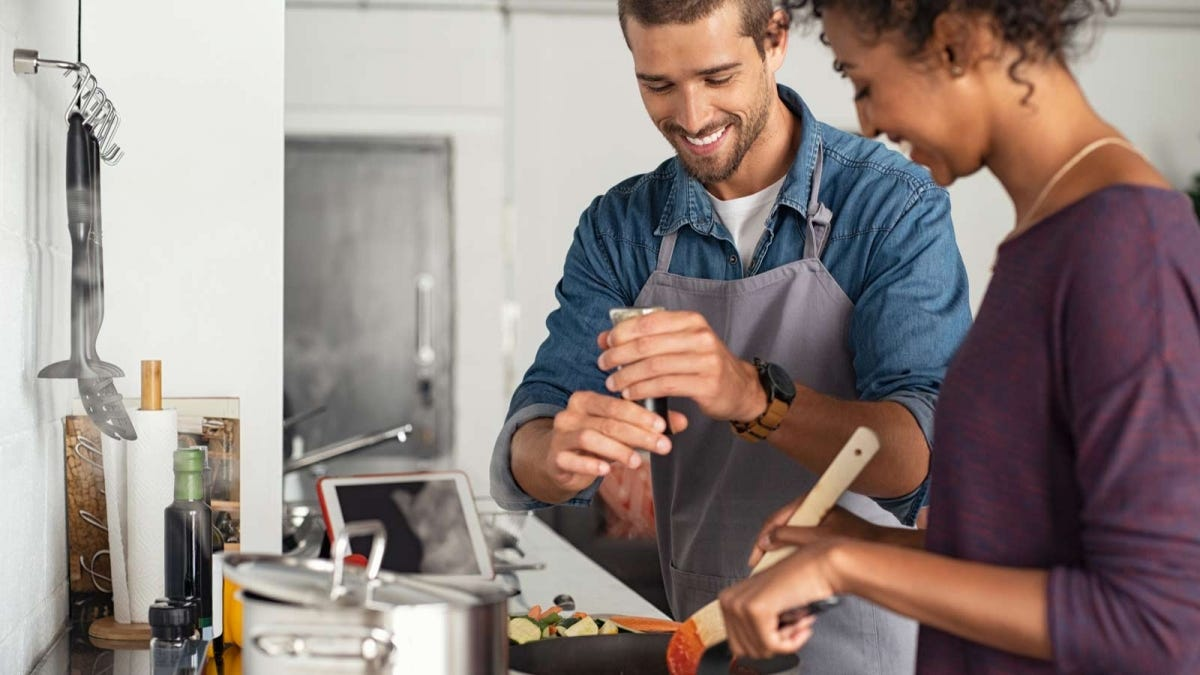 young man cooking with his girlfriend and adding fresh cracked pepper to the pan