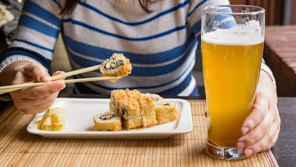 Woman eating sushi with a beer.