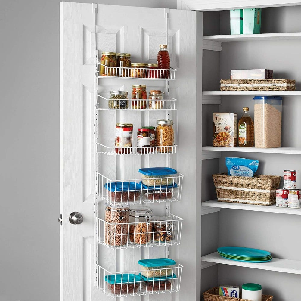 Open pantry closet with a wire rack storing jars hanging off the door