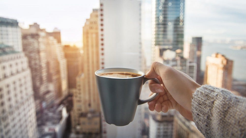 Woman holding a cup of coffee up in the sun, against the cityscape outside her window.