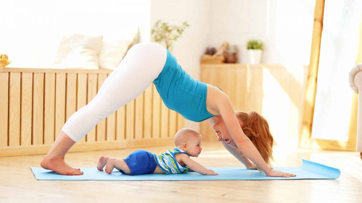 Woman doing yoga with a baby on the mat.
