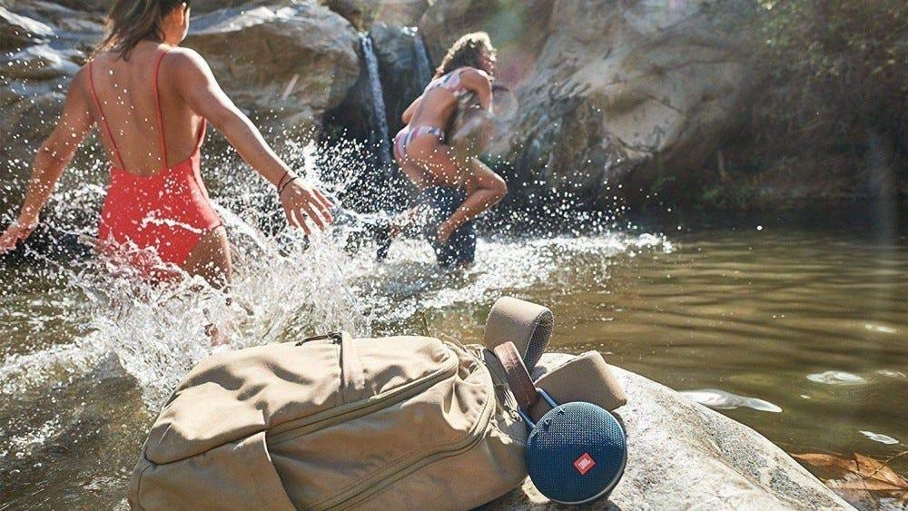 Emberek, akik egy kis időt élveznek a tóban, vízálló Bluetooth hangszóróval a közelben.