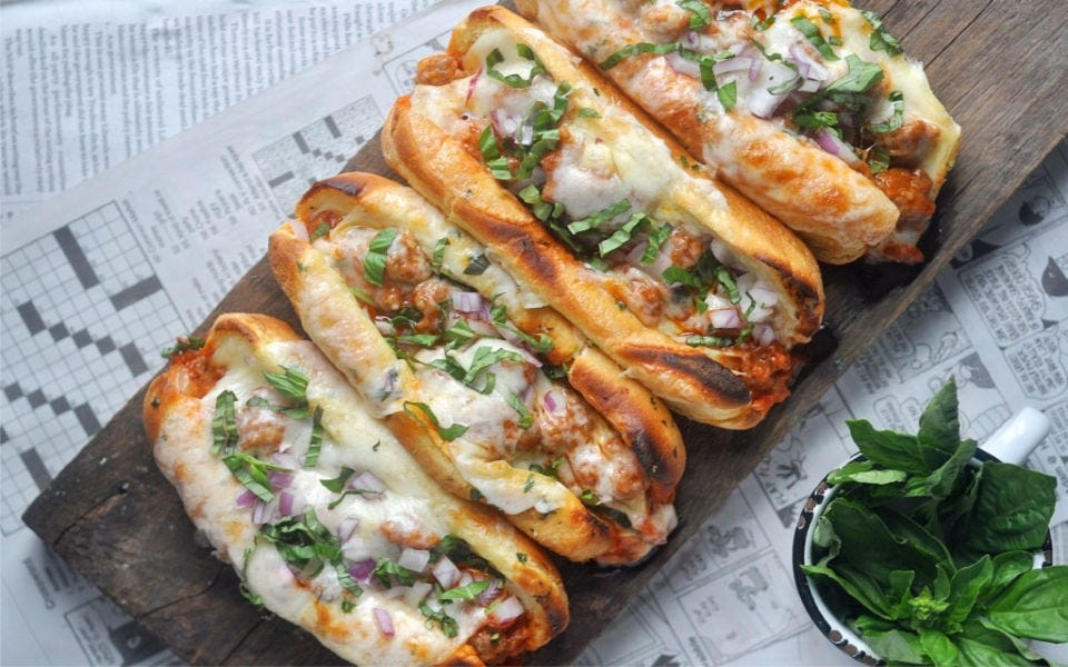 Four fully loaded sausage sandwiches, topped with melted cheese and fresh basil.