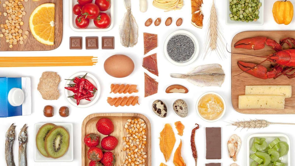 Various foods know to cause allergic reactions laid out on a white background.