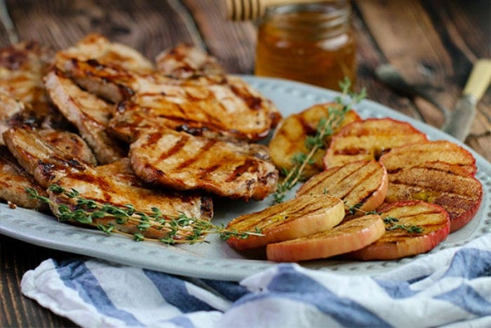 A plate of grilled porkchops and cinnamon apple slices