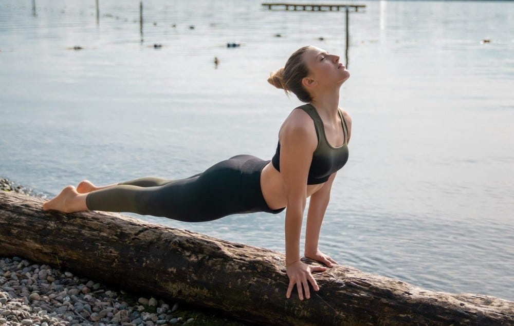 Woman doing yoga on a tree trunk in the lake.