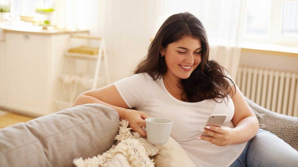 A young woman sitting on a couch drinking coffee, smiling while using a happiness app on her smartphone.