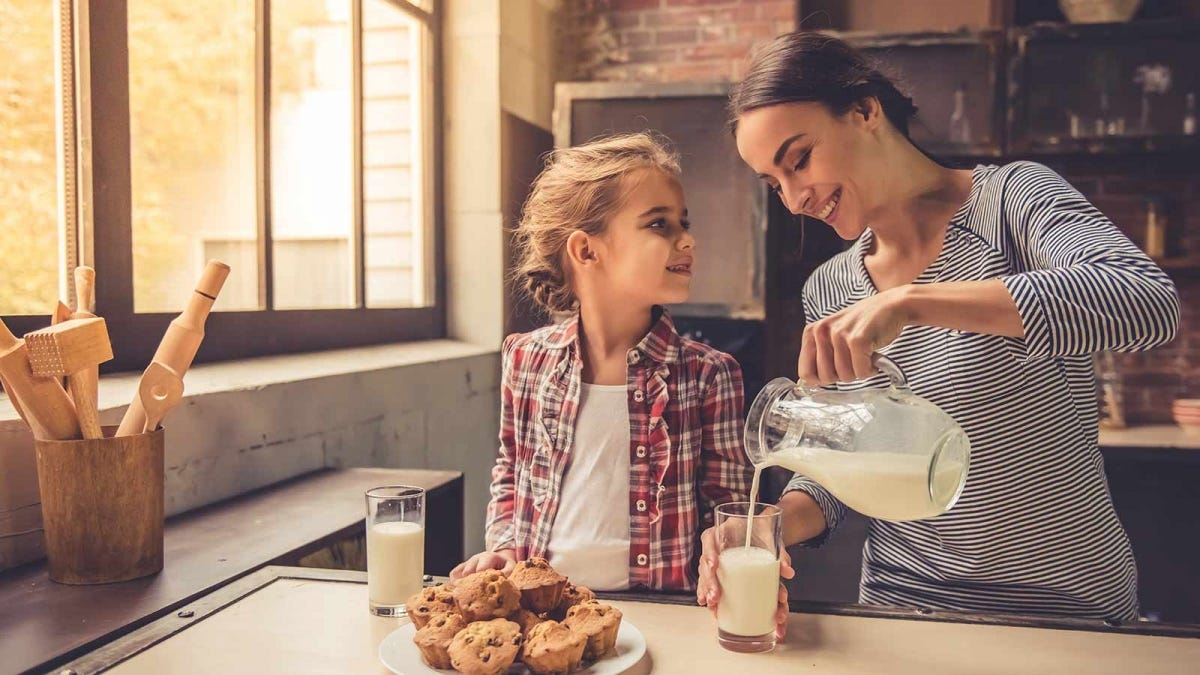 woman pouring a tall glass of milk for her child and herself