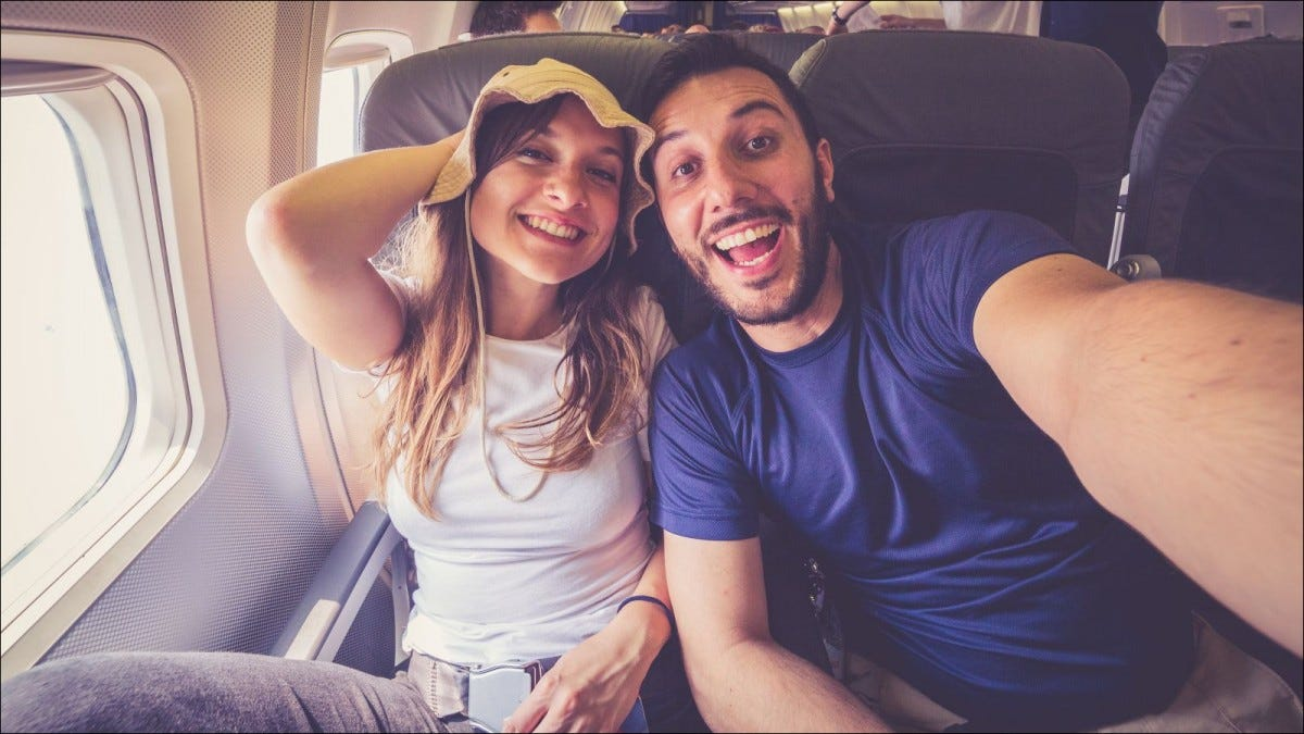 happy young couple taking selfie on airplane