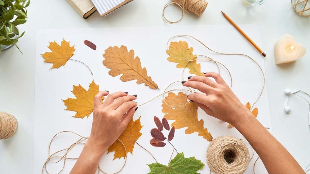 A woman working on fall-themed leaf crafts.