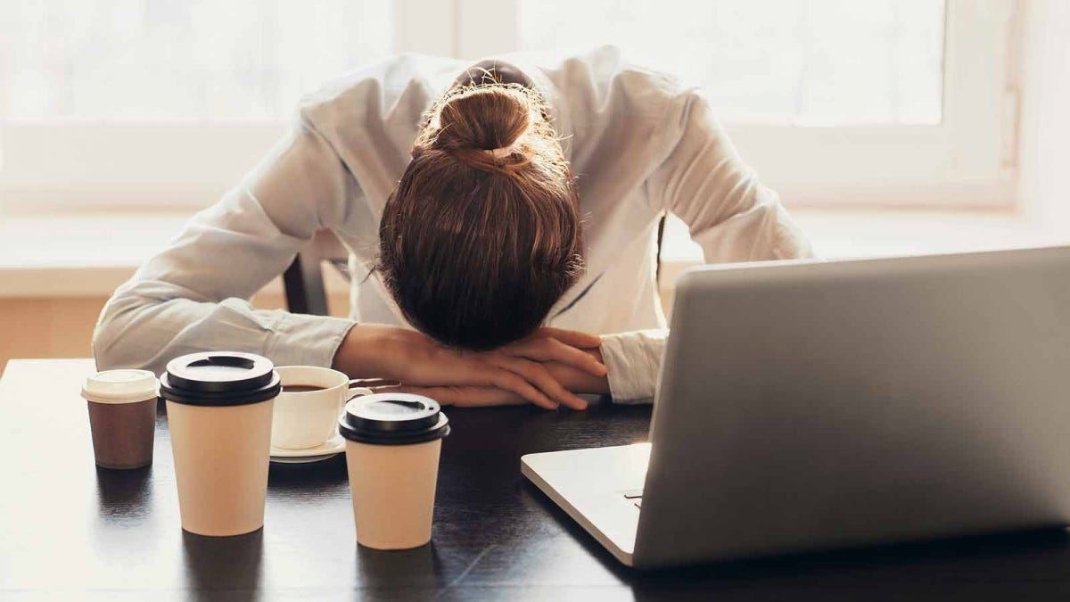 Woman sleeping on her desk surrounded by coffee cups