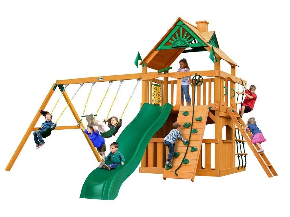 Eight children playing on the Chateau Clubhouse Wooden Playset swings, trapeze bar, slide, climbing wall, and clubhouse.