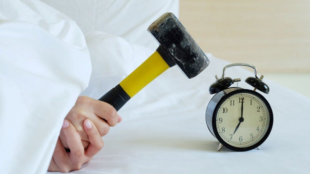 Someone under the covers getting ready to hit an alarm clock with a mallet.