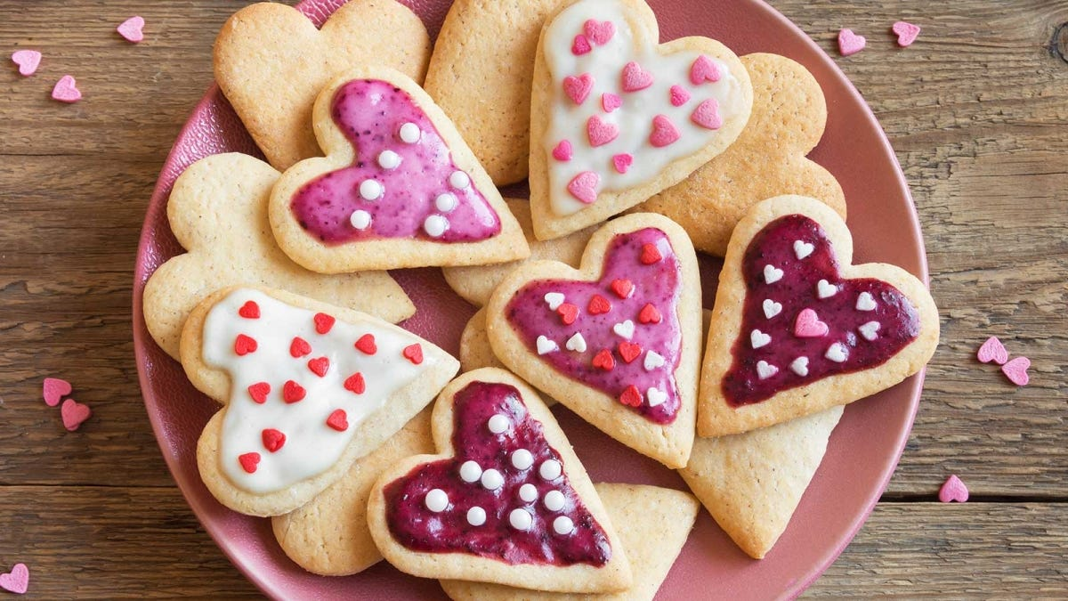 A plate loaded with heart-shaped frosted cookies.