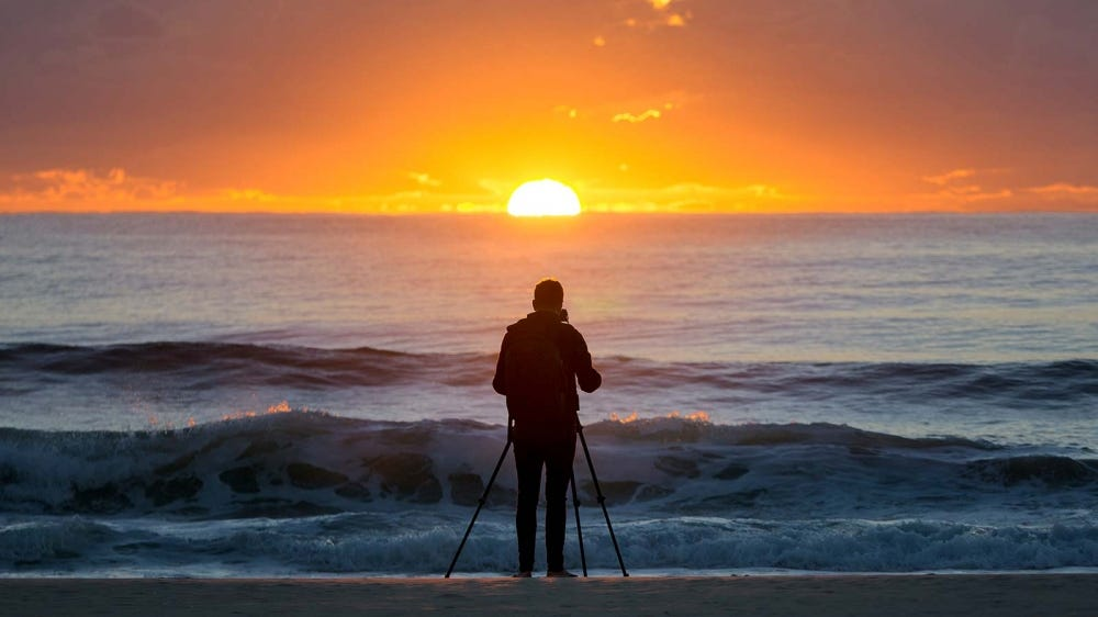 A photographer taking a picture of the sun rising over the Atlantic ocean.
