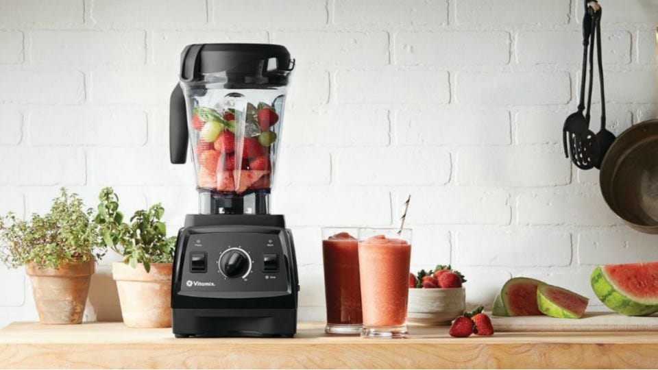 A vitamix blender with fresh fruit inside the glass container, with two freshly made smoothies and cut fruit on the side.