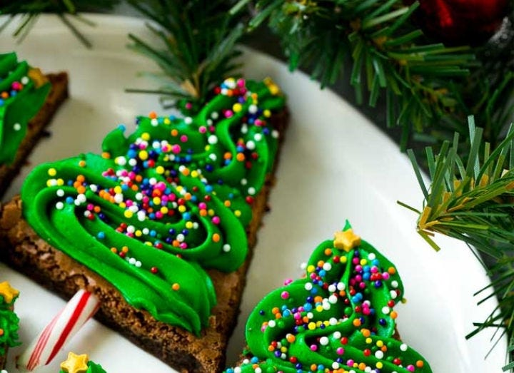 Three brownies decorated with green icing and sprinkles to look like mini Christmas trees.