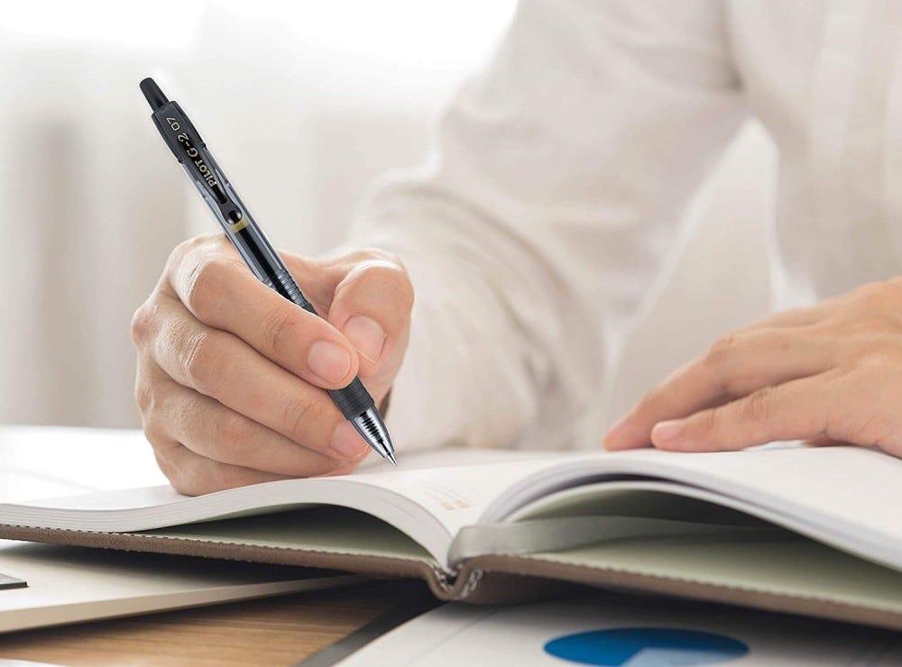 دستی با استفاده از قلم Pilot G-2 برای نوشتن در یک دفترچه یادداشت.