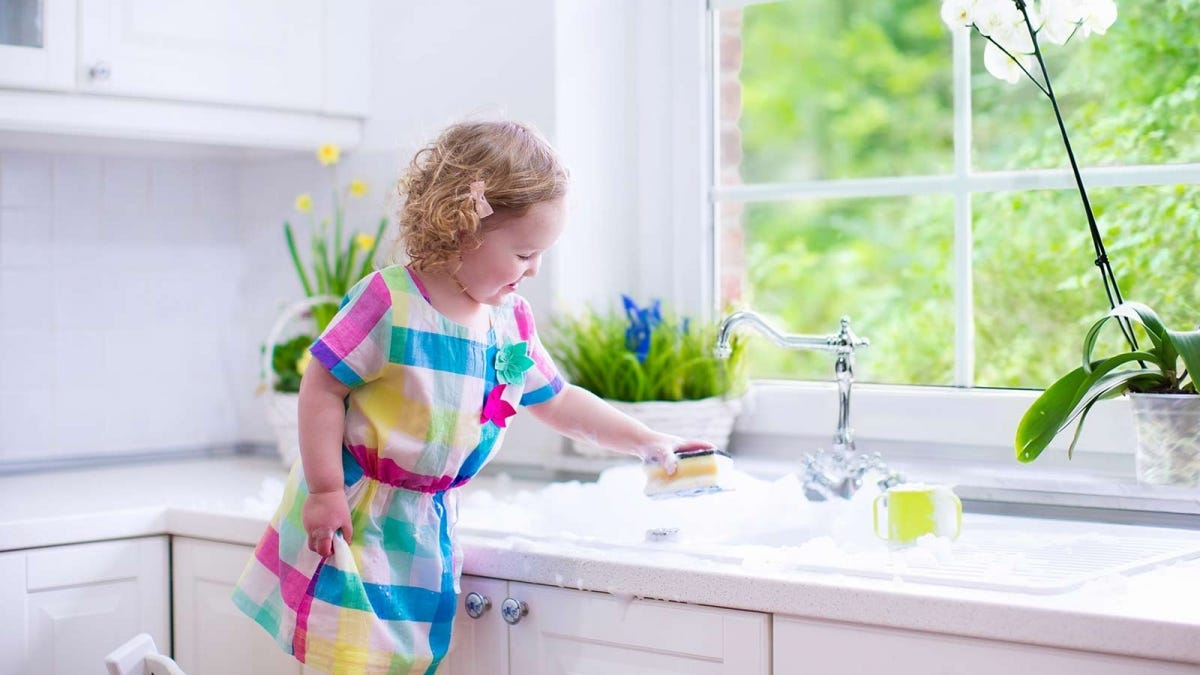 Little girl playing with sponges and soap in a kitchen sink.