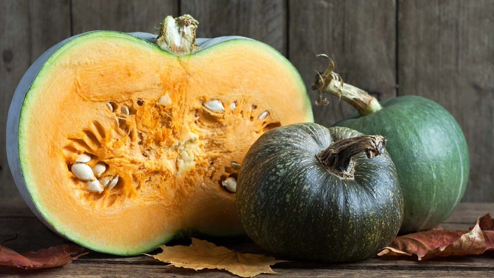A buttercup squash that's been cut open, sitting on a rustic table.