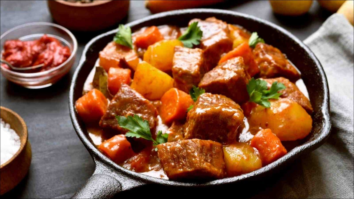 Beef meat stewed with potatoes and carrots in cast iron pan