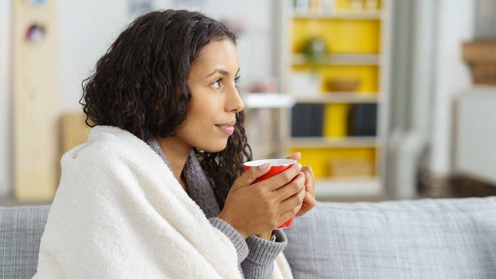 A woman drinking a warm drink, wrapped up in a blanket sitting on her couch.