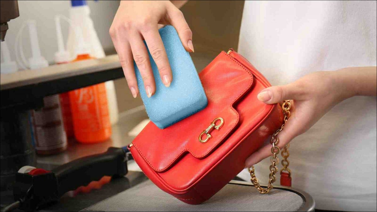 Woman washing purse with sponge