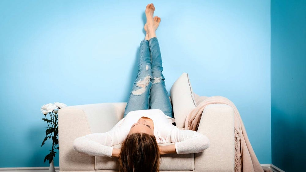 Woman laying on a chair with her feet up.