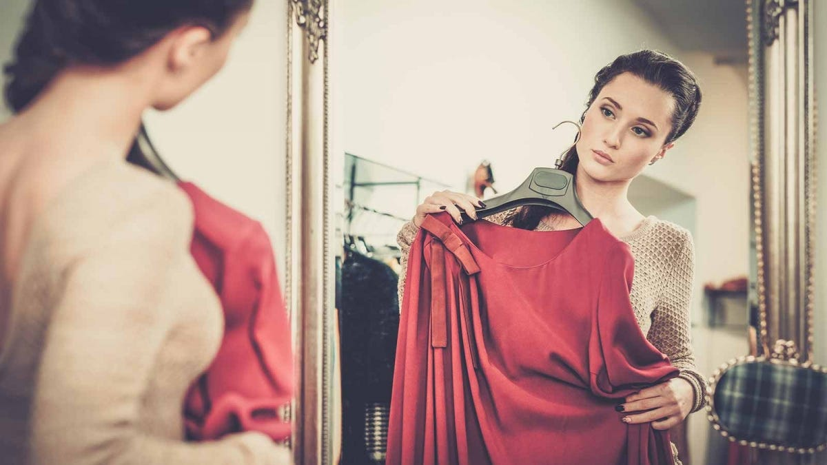 A woman holding a dress to her body and looking at herself in a mirror.