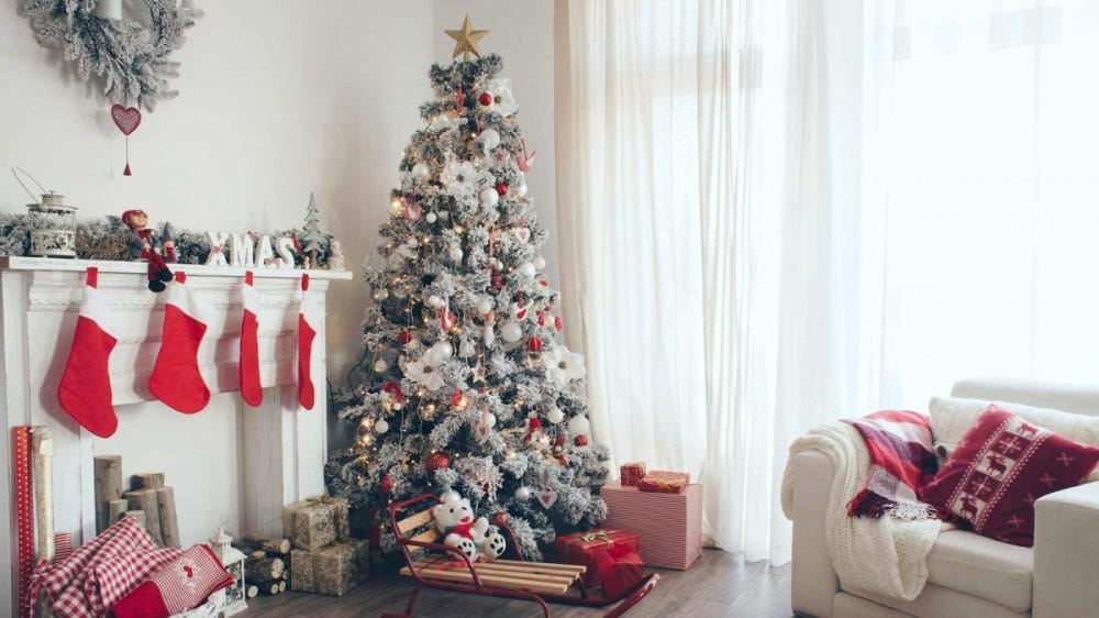 A living room is decorated for Christmas with a flocked tree, red stocking on the mantle, and Christmas pillows on the couch.