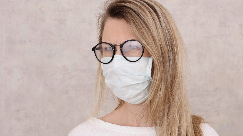Woman wearing a mask, struggling with fogged up lenses.