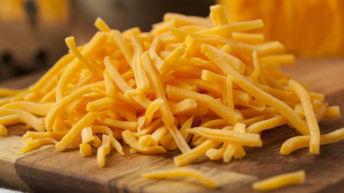 A pile of shredded cheddar cheese on a cutting board.