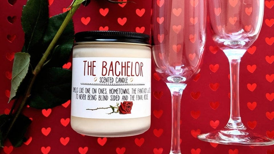 The Bachelor candle on a heart background with roses and wine glasses.