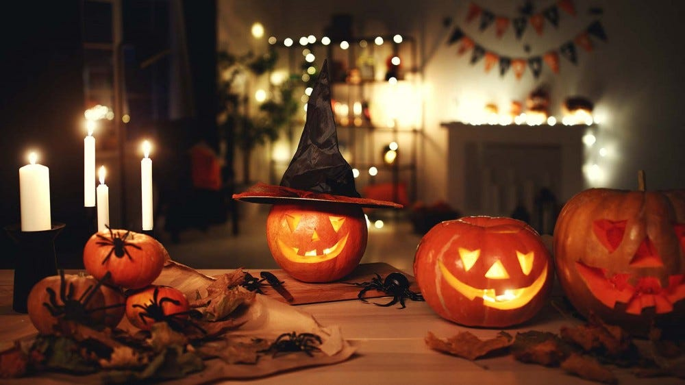 Three jack-'o-lanterns on a table surrounded by candles and spiders.