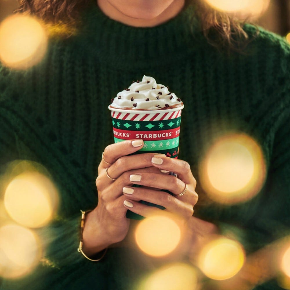 A woman holds a holiday Starbucks cup.