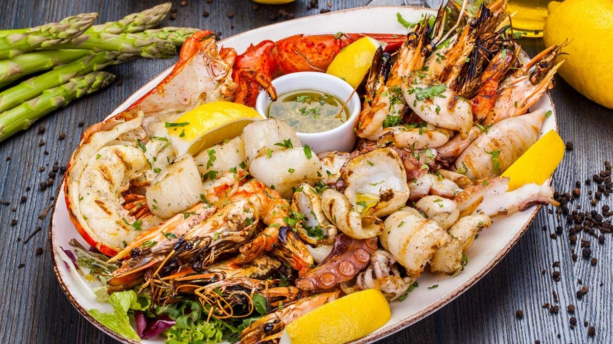 A seafood platter loaded with a variety of seafood, lemon wedges, and butter.