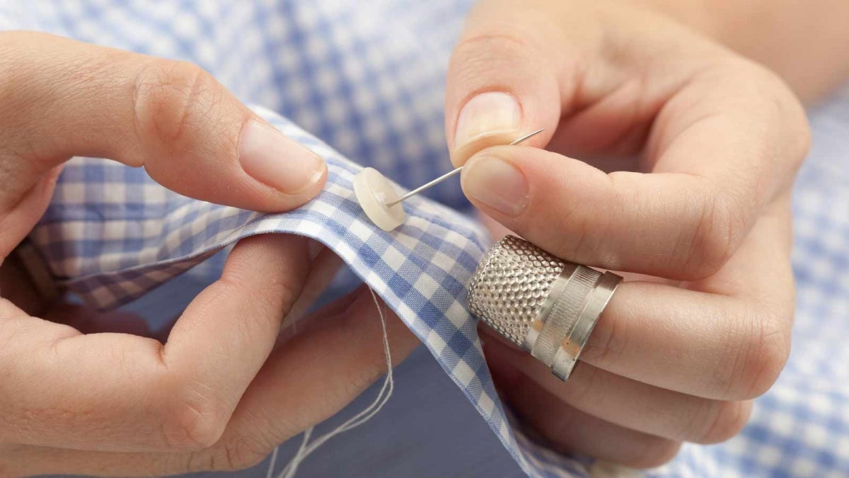 Person hand sewing a button onto the front of a shirt