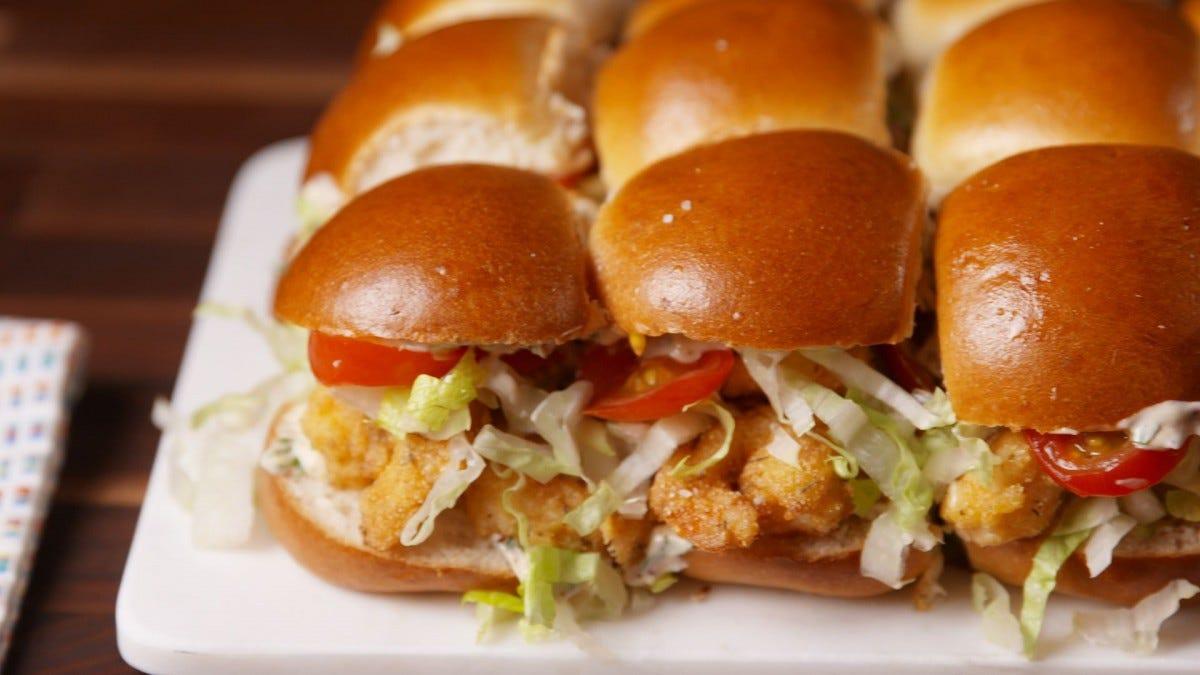 A plate full of shrimp po'boy sliders.