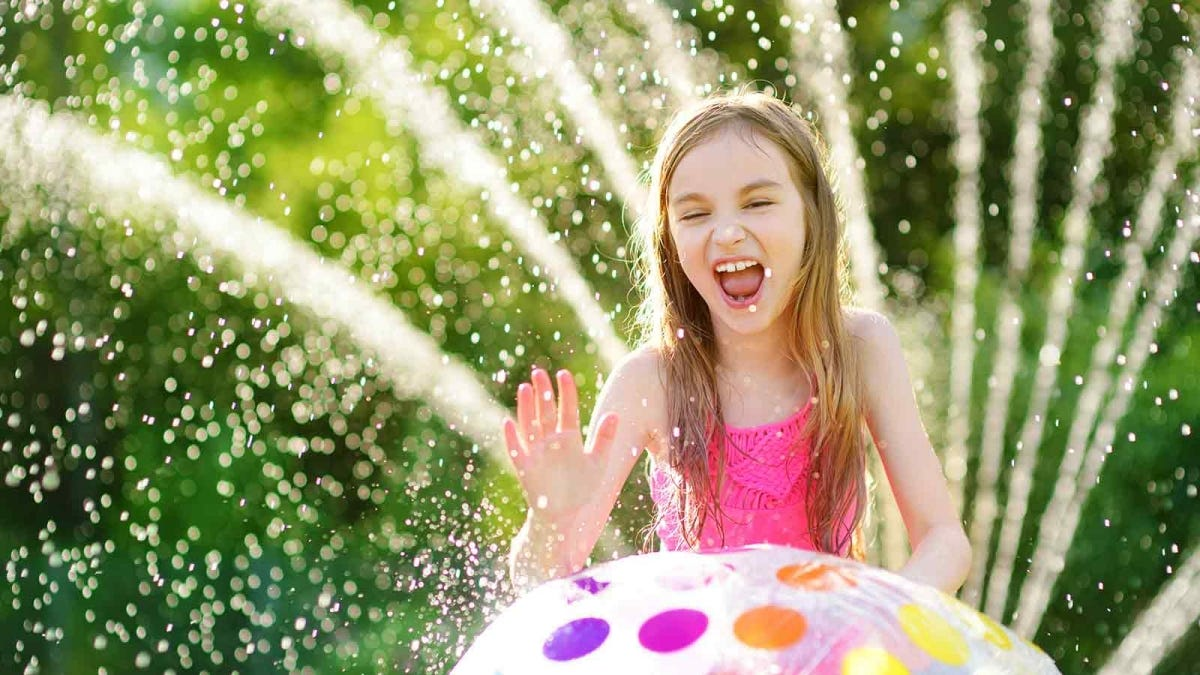 Girl playing in the sprinkler